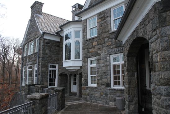 Granite home rear with view of portico arches